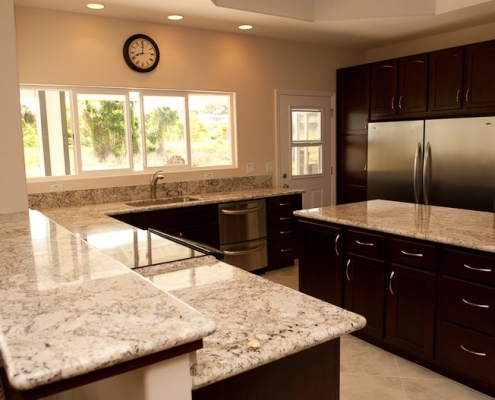 Dark cafe kitchen cabinets with light countertops and backsplash 2